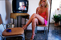 Dressed in her favorite dress, Alexander waits for the evening to come so she can go out to a club. She watches Cuban television--and the daily parade of children demonstrating their support of Elian Gonzalez (the Cuban boy who was ship wrecked with his mother while on his way to the United States. His mother died and the boy became a political football between Fidel and the Miami Cuban community.) Alexander is comfortable with her life as a transvestite. She was issued an identification card by the government as a woman