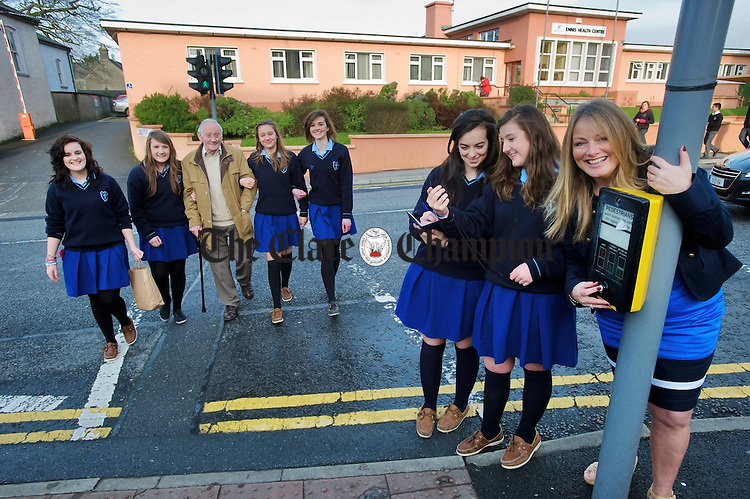 Colaiste Muire Ennis transition year students; Roisin Curran, Aoife Sheehan, Jenny Hansbury, and Muireann O Shea help senior citizen Michael Collins across the road at a pedestrian crossing as  Sarah O Reilly and Orla Bredin do the timing as part of their YSI project. They they have put a submission to Ennis Town Council, with support from Councillor Mary Howard, at right, to have the timing for traffic lights at pedestrian crossings increased to enable elderly people to cross the road with greater ease and safety. Photograph by John Kelly.