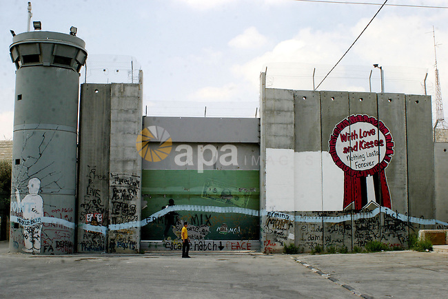 Palestinian boys walk beside the controversial Israeli barrier in the West Bank town of Bethlehem on July 6 2009. Photo by Najeh Hashlamoun