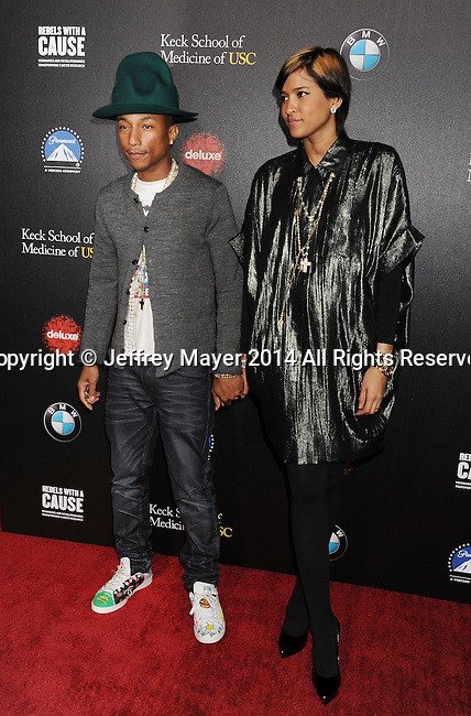 HOLLYWOOD, CA- MARCH 20: Singer/musician/producer Pharrell Williams (L) and Helen Lasichanh arrive at the 2nd annual Rebel With a Cause Gala held at the Paramount Studios on March 20, 2014 in Hollywood, California.