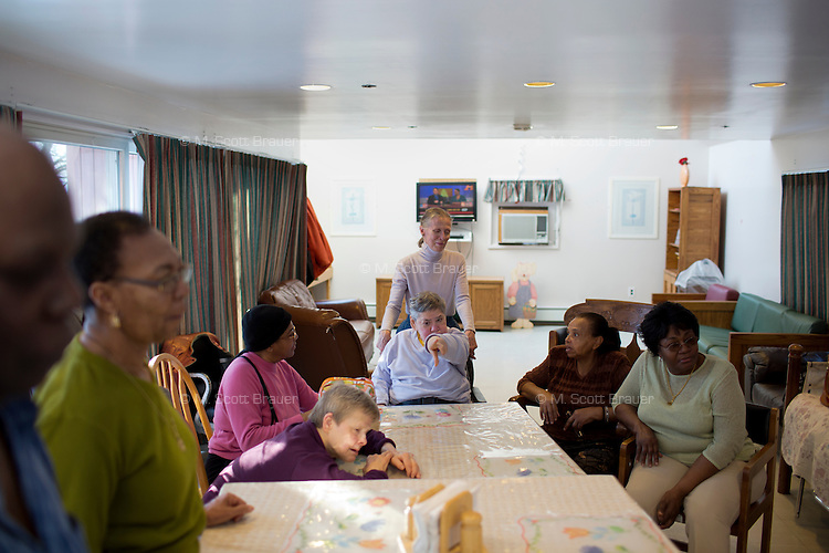 Residents, caregivers, and family members gather around a table in the residences at Malone Park at the Fernald Developmental Center in Waltham, Massachusetts, USA.