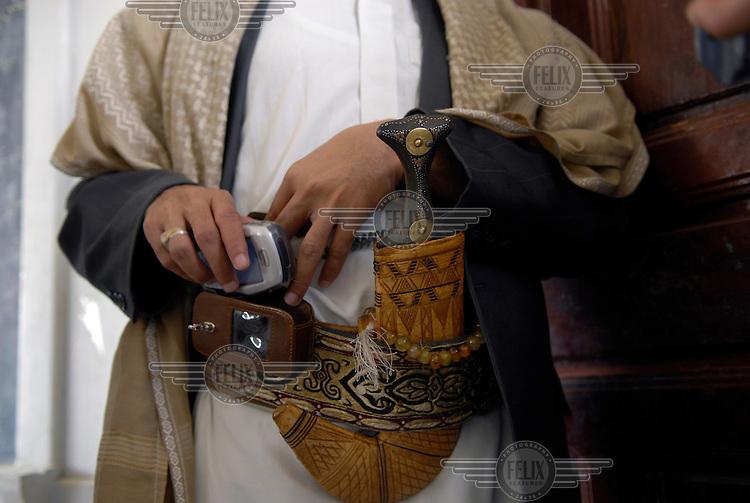 A school teacher wearing a jambiya (Yemeni dagger) and a mobile phone around his waist.