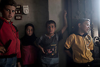 In this Sunday, Sep. 29, 2013 photo, brothers and sister of ABDU EL KADER (not pictured) are photographed at their family house in Madaya village after attended classes in the public school in the Idlib province countryside of Syria. Children have come back to school in the rebel controlled territory despite the constant threaten of shelling and the ongoing fighting, and public schools still operating financially under the Syrian government administration. (AP Photo)