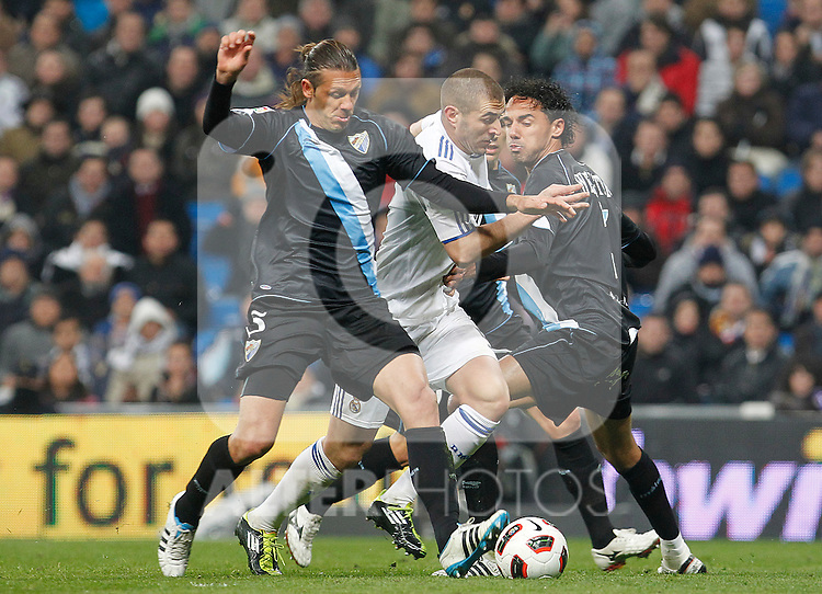 Real Madrid's Karim Benzema (c) and Malaga's Martin Gaston Demichelis and Weligton Robson during La Liga match.March 3,2011. (ALTERPHOTOS/Acero)
