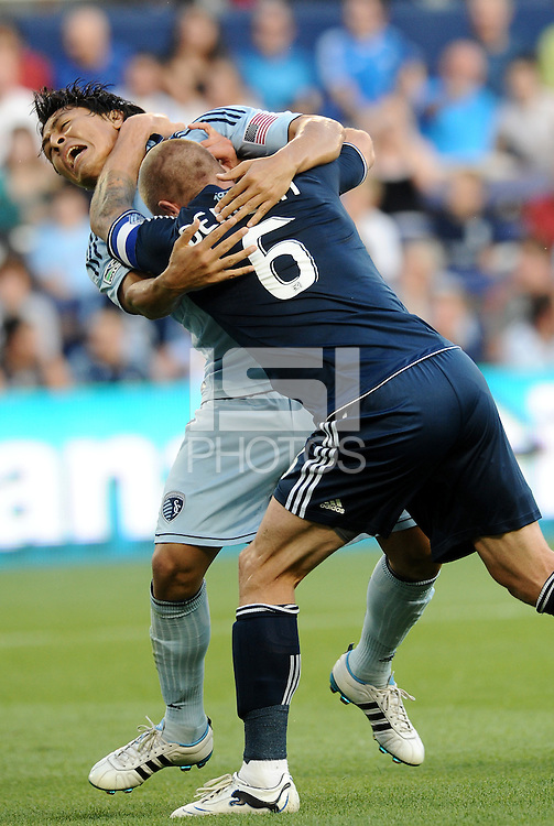 Vancouver Whitecaps captain Jay DeMerit tangles with Sporting KC midfielder Roger Espinoza... Sporting KC defeated Vancouver Whitecaps 2-1 at LIVESTRONG Sporting Park, Kansas City, Kansas.