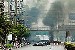 16 MAY 2010 - BANGKOK, THAILAND: Smoke rises over the Bangkok skyline from burning tire barricades along Rama IV Road near Lumpini boxing stadium Sunday. Thai troops and anti government protesters clashed on Rama IV Road again Sunday afternoon in a series of running battles. Troops fired into the air and unidentified snipers shot at pedestrians on the sidewalks. At one point Sunday the government said it was going to impose a curfew only to rescind the announcement hours later. The situation in Bangkok continues to deteriorate as protests spread beyond the area of the Red Shirts stage at Ratchaprasong Intersection. Many protests now involve people who have not been active in the Red Shirt protests and live in the vicinity of Khlong Toei slum and Rama IV Road. Red Shirt leaders have called for a cease fire, but the government indicated that it is going to go ahead with operations to isolate the Red Shirt camp and clear the streets.      PHOTO BY JACK KURTZ