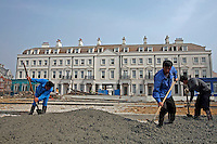 Migrant workers operating on the construction site of the exclusive Thames Town Villas development in Shanghai, China. A villa in Thames Town cost an average of 400,000 euros, while a worker earns less than 3 euros a day. Such disparities between the rich and poor have driven the ongoing National People's Congress meeting to delay the voting of a key legislation that is suppose to protect the ownership of private property..10 Mar 2006