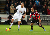 (L-R) Kyle Bartley of Swansea marked by Junior Stanislas of Bournemouth during the Barclays Premier League match between Swansea City and Bournemouth at the Liberty Stadium, Swansea on November 21 2015