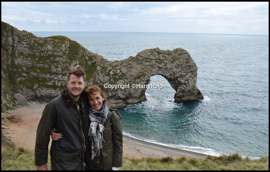 BNPS.co.uk (01202 558833)Pic: HarryRolph/BNPS<br /> <br /> Harry Rolph and Eleni Kostantaki posing for a photo in front of Durdle Door in Dorset,  just after the proposal.<br /> <br /> Love on the rocks...<br /> <br /> The wedding proposal of a couple inadvertently caught on camera no longer has a cliffhanger ending - as they have been found and confirmed they are engaged.<br /> <br /> Tracey Hollis-Rowe, 44, was photographing idyllic Durdle Door in Dorset when she captured a man getting down on one knee and his shocked girlfriend putting her hand to her mouth.<br /> <br /> Not wanting to infringe on the tender moment Tracey quickly walked away but she later put the photo on social media and appealed for the couple to get in touch.<br /> <br /> The story was picked up by local and national media and shared on Facebook and Twitter before Harry Rolph contacted Tracey to tell her he was the man in the picture and his girlfriend Eleni Kostantaki had said yes.