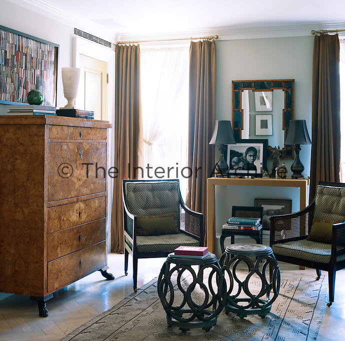 The living room is furnished with a 19th century Karelian secretary, a pair of English Regency armchairs and bronze garden stools