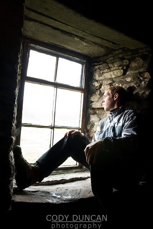 man sits looking out window of simple stone bothy at Rackwick Bay on the island of Hoy, Scotland
