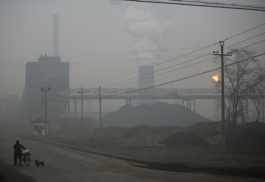 A resident walks down a a typical Linfen road, engulfed in pollution from a nearby coking plant.