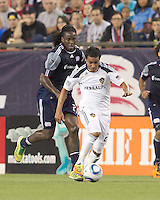 Los Angeles Galaxy forward Miguel Lopez (25) dribbles as New England Revolution forward Shalrie Joseph (21) closes. In a Major League Soccer (MLS) match, the Los Angeles Galaxy defeated the New England Revolution, 1-0, at Gillette Stadium on May 28, 2011.