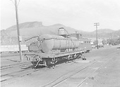End side view of water car - tank on flat car - taking water with Silver Vista and caboose 0586 in background.<br /> D&amp;RGW  Durango, CO