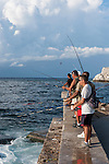 Havana, Cuba; several men fishing along the sea wall at the entrance to Havana harbor in the late afternoon sunlight
