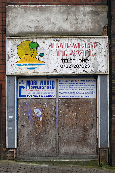 An abandoned and neglected shopfront of a travel agent's office in Stoke-on-Trent city centre. The economic downturn has hit the retail sector particularly hard, adding to the region's losses of employment and identity experienced by the dramatic demise of once world-renowned industries.
