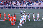 Teams walk in single file onto the center of the field for introductions before a game.