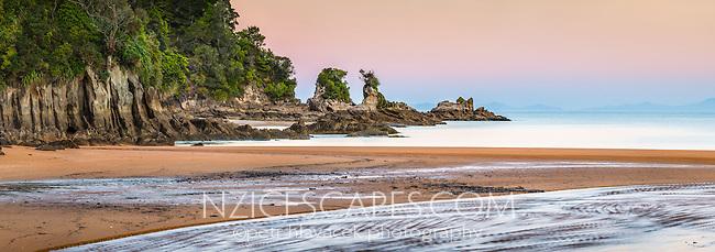 Coastal rock formations under pastel colours of twilight after sunset on Totaranui beach on Abel Tasman Coast Track, Abel Tasman National Park, Nelson Region, South Island, New Zealand, NZ