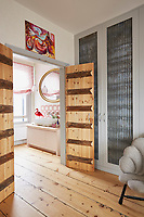 Built-in floor-to-ceiling wardrobes in the main bedroom. The room has a pair of rustic style wooden doors and a wood floor.