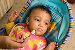 Infant development 9 month old baby girl fed by spoon turning head to reject more food