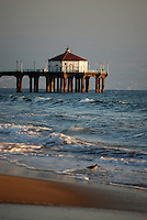 Manhattan Beach, California, pier at dusk with waves,sand and bird