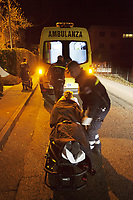 Switzerland. Canton Ticino. Viganello. Night scene for a medical emergency intervention. A senior man lying down on an emergency medical stretcher is being transported from home. The elderly man is suffering from a heart problem and needs to be brought to hospital for a medical examination. Three paramedics wear blue uniforms and work for the Croce Verde Lugano. The man and the woman (L and center) are professional certified nurses, the third (R) is a volunteer specifically trained in emergency rescue. The Croce Verde Lugano is a private organization which ensure health safety by addressing different emergencies services and rescue services. Volunteering is generally considered an altruistic activity where an individual provides services for no financial or social gain to benefit another person, group or organization. Volunteering is also renowned for skill development and is often intended to promote goodness or to improve human quality of life. Viganello is a quarter of the city of Lugano. 20.01.2018 © 2018 Didier Ruef