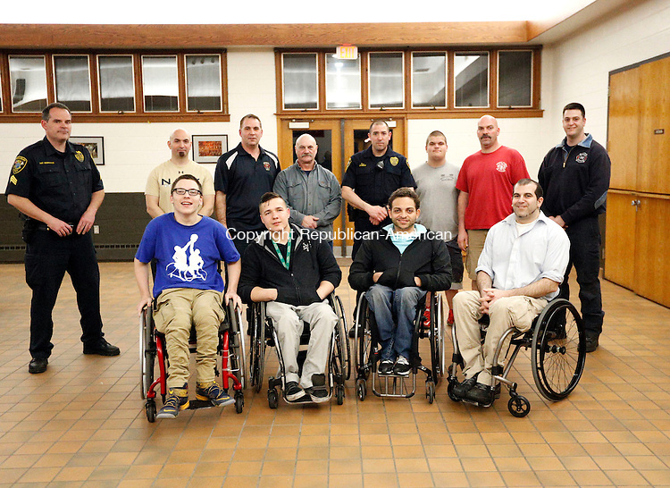 Middlebury, CT- 10 March 2016-031016CM03-  Middlebury volunteer firefighters and Middlebury police officers gather around a wheelchair basketball team at the Middlebury firehouse on Thursday.  The team features local, David Desmarais, show in the front row at left.  The team has made it to the nationals in Kentucky and will play police and firefighters in a charity basketball game on March 21.  Christopher Massa Republican-American