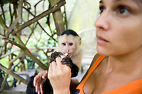 Vanessa Lizano with a Capuchin monkey at her Costa Rica Wildlife Sanctuary run by Vanessa and her family. Moin, Limon, Costa Rica.
