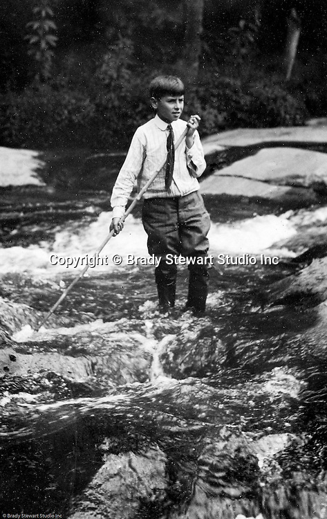 Stewart Township:  View of Homer Stewart Jr playing with a stick in Bear Run Creek with his Sunday school clothes on 1905.  Stewart family went to visit Brady family relatives that lived in Stewart Township.