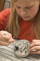 Kinder gießen Tierspur aus Gips, Mädchen reinigt Gipsabdruck vom Trittsiegel, der Fußspur von einem Reh mit einem Pinsel von Erdresten