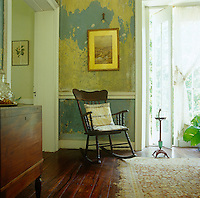 In the living room of a house in Jamaica layers of paint and wallpaper have been scraped away and left unrestored for an interesting decorative effect which also reveals the history of the house