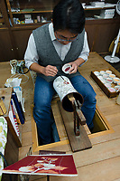 An artisan paints enamel on to a vase. Ando Cloisonne, Nagoya, Aichi Prefecture, Japan, February 26, 2018. Family-owned and run Ando Cloisonne was founded in the 1880s and is the only large manufacturer of cloisonne metalware left in Japan. The cloisonne enamelling process is technologically complex and a single work may feature over 50 colours.