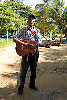 Black Nicaraguan man playing the guitar and singing on Big Corn Island, Nicaragua