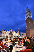 Turisti seduti di sera nei caffe' all'aperto in Piazza San Marco, a Venezia. Sullo sfondo, la Basilica e il campanile.<br /> Tourists sit at outdoor cafes in St. Mark's Square, Venice, in evening light. In background, St. Mark Basilica and the bell tower.<br /> UPDATE IMAGES PRESS/Riccardo De Luca