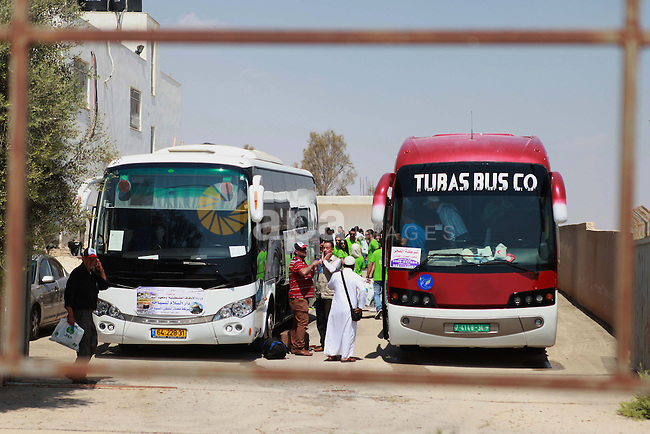 A bus carrying Palestinian Muslim pilgrims leaves en route to Al-Karama crossing between the West Bank and Jordan near Jericho, on Sept. 16, 2014, before leaving for the annual hajj pilgrimage to the holy city of Mecca. Hundreds of Palestinian pilgrims are leaving West Bank through the Al-Karama crossing on their way to Mecca, Saudi Arabia, for hajj. Photo by Shadi Hatem