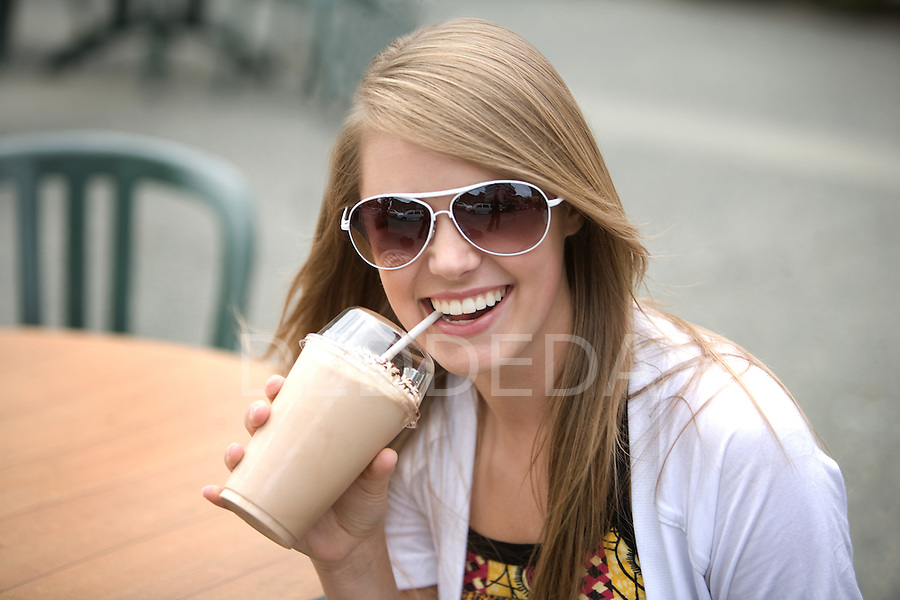 A pretty blond teenage girl wearing sunglasses drinks a milkshake and smiles for the camera outside in Victoria, British Columbia, BC, Canada.
