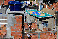 Woman takes sun at her house´ slab-cover - Brazil´s flag painted on next house´s roof, in reference to the Brazilian soccer team. Since 2008 Santa Marta has a Pacifying Police Unit ( Unidade de Polícia Pacificadora, also translated as Police Pacification Unit ), abbreviated UPP, a law enforcement and social services program which aims at reclaiming territories, more commonly favelas, controlled by gangs of drug dealers.