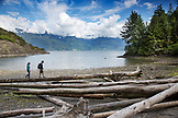 CANADA, Vancouver, British Columbia, Eric and Stepahnie Petersen walk on driftwood logs at Brigade Bay on Gambier Island, in the Howe Sound with the Britannia Range in the distance