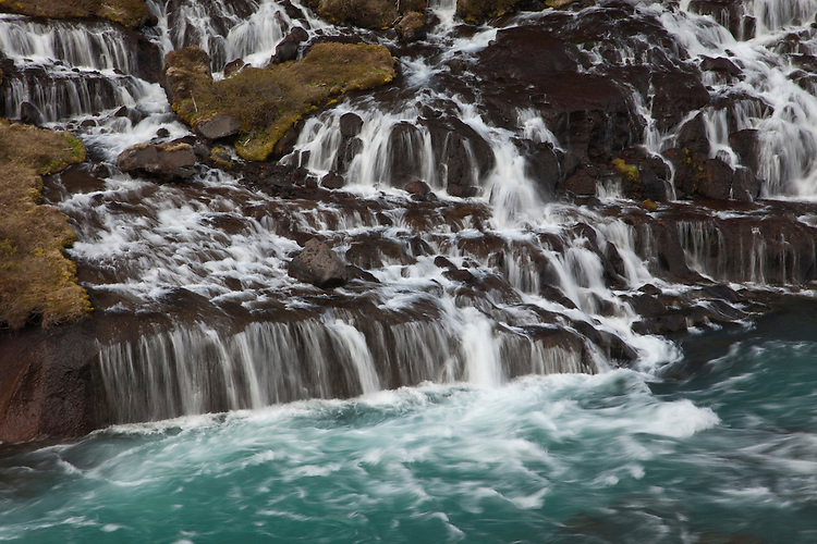 a series of cascades flow out from beneath an ancient lava flow at Hraunfossar waterfalls