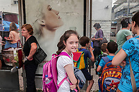 Albania. Gjirokastër. A group of boys and girls, all schoolchildren with backpack on their back, wait with other women at the bus stop. An advertisement with a beautiful model for a new perfume. Gjirokastër is a city in southern Albania. 23.05.2018 © 2018 Didier Ruef