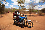 Maasai villagers arriving by motorbike at the Predator Compensation Fund Pay Day, Mbirikani Group Ranch, Amboseli-Tsavo eco-system, Kenya, Africa, October 2012