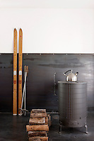A pair of vintage skis is propped beside a contemporary wood-burning stove in the living area