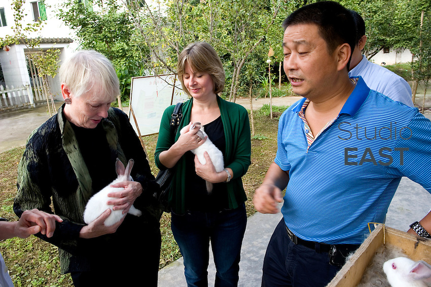 Citi Foundation president Pamela Flaherty (left) and Citi Foundation director Paula Bennett (center) pet rabbits belonging to rabbit farmer Ren Xuping (right) in Dayi, near Chengdu, Sichuan province, China, on September 11, 2010. Photo by Lucas Schifres/Pictobank
