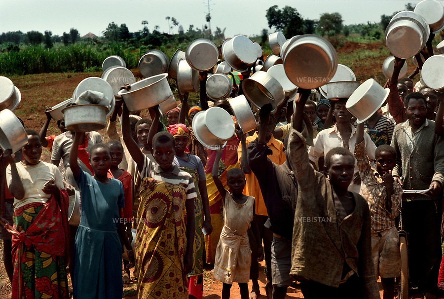1994. Burundi. Lake Cyohoha. Maza Camp. During the Rwandan Genocide, refugees who have just received big tins wait for flour distribution. Burundi. Lac Cyohoha. Camp de Maza. Pendant le génocide au Rwanda, des réfugiés à qui on a donné des gamelles, attendent une distribution de farine.