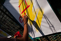 """A Colombian sign painter's hand is seen writing letters with a brush on a music party poster in the sign painting workshop in Cartagena, Colombia, 18 April 2018. Hidden in the dark, narrow alleys of Bazurto market, a group of dozen young men gathered around José Corredor (""""Runner""""), the master painter, produce every day hundreds of hand-painted posters. Although the vast majority of the production is designed for a cheap visual promotion of popular Champeta music parties, held every weekend around the city, Runner and his apprentices also create other graphic design artworks, based on brush lettering technique. Using simple brushes and bright paints, the artisanal workshop keeps the traditional sign painting art alive."""
