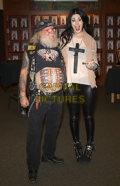 """fan & Kat Von D (Katherine von Drachenberg).Kat Von D holds a book signing for hre new book, """"Go Big or Go Home"""" at Barnes and Noble on Rainbow in Las Vegas, Las Vegas, NV., USA..May 26th, 2013.full length white black print cross crucifix top beige cardigan tattoos funny mouth open stomach belly duff beer 6 six pack the simpsons hat beard facial hair leather trousers .CAP/ADM/MJT.© MJT/AdMedia/Capital Pictures"""