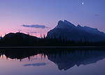 The moon shines high above while the Vermillion lakes reflect Mount Rundle in the twilight.