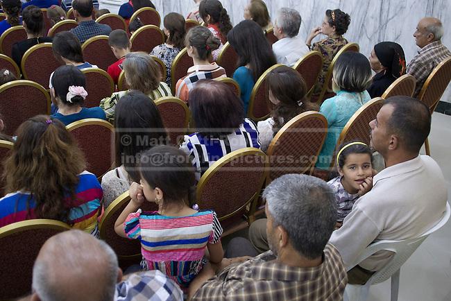5 year old Iraqi Christian Mosul refugee Rania Minowar Salim (R) looks up during a service held at the Seramer Christian Academy in Hamdaniyah, Iraq.