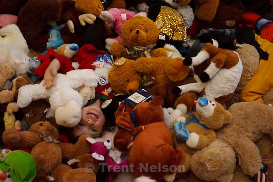 Sarah Conder (older), Savana Conder, Connor Riches and Abi Riches play in a pile of donated teddy bears and stuffed animals, Thursday, December 17, 2009 at the Family Support Center in Taylorsville. 7,463 teddy bears are being delivered to the Salt Lake County Family Support Center and the Utah Valley Family Support & Treatment Center for children.