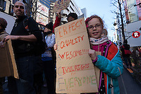 A young girl with a sign at a protest march and rally organised by the Alliance for an Inclusive America group against the perceived anti-Muslim and anti-foreigner immigration policies of President Donald Trump, Shibuya, Tokyo, Japan. Sunday February 12th 2017. The Alliance of an Inclusive America is a multi-faith non-partisan group. About 250 Americans, other ex-pats and japanese people took part in the march to show people around the world they reject the Executive Order President Trump enacted at the end of January, indefinitely suspending the resettlement of Syrian refugees and temporarily banning people from seven majority Muslim countries from entering the United States.